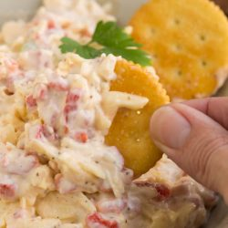 Using gouda cheese instead of the traditional cheddar in Gouda Pimento Cheese gives this recipe a delicious twist. Pimento Cheese is a popular Southern spread consistng of cheese, pimento peppers, mayonaise, and seasonings. This cheesy spread can be used in a sandwich, or a grilled sandwich, to top burgers, or as a dip with crackers. It can be eaten hot or cold. And, it's great for picnics and tailgating.