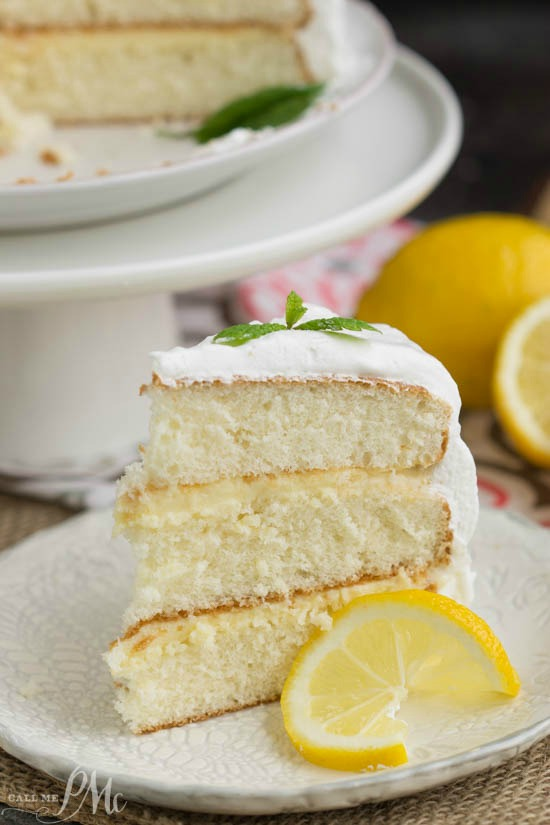 Lemon Cake is a tender white cake filled with tart lemon curd and covered with a fluffy whipped cream frosting.