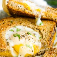 Egg in a Hole Grilled Cheese a simple breakfast recipe of perfectly prepared sunny side up eggs in a grilled cheese sandwich. #grilled #cheese #egginahole #eggs #sunnysideup #grilledcheese #recipe #breakfast #sandwich