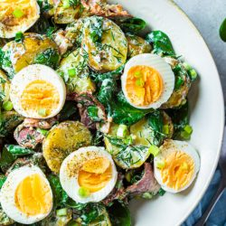 Traditional potato salad with bacon and eggs in a white bowl. Picnic food concept.