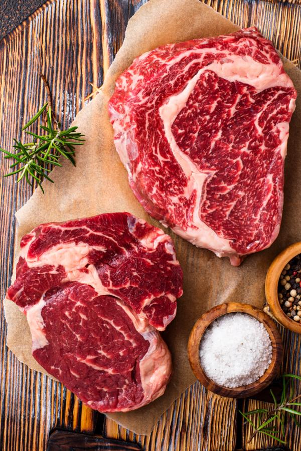 Raw Ribeye on cutting board with seasonings