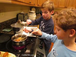 2 kids frying mini corndogs