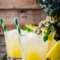 Fresh pineapple juice in two glasses with ice and mint leaves on dark rustic background