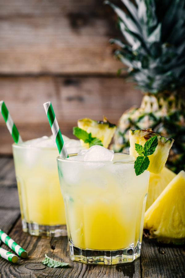 Tequila Pineapple Cocktail - Fresh pineapple juice in two glasses with ice and mint leaves on dark rustic background