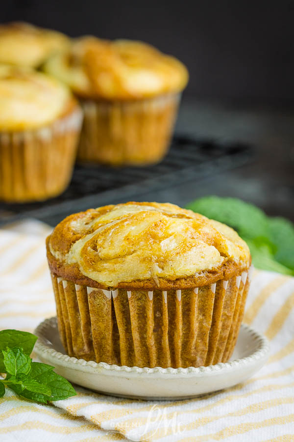 Perfectly soft and moist, Pumpkin Cream Cheese Swirl Muffins are topped with a luscious swirl of cheesecake. #muffins #pumpkin #easy #breakfast #recipe #cheesecake #brunch #pumpkinpie