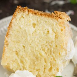 Dessert Recipe. This Coconut Cream Cheese Pound Cake recipe is crazy delicious. Dense and buttery this pound cake is topped simply with a sprinkle of powdered sugar then served with whipped cream and berries. This rich, dense, buttery cake is dessert perfection.