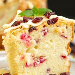 Holiday Greek Yogurt Cranberry Pound Cake is tender, buttery, and spiked with tart cranberries. Perfect for the holidays, this dessert is festive, fluffy, and delicious.
