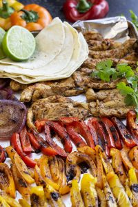 Healthy 20 Minute Chili Lime Sheet Pan Chicken Fajita Recipe is an easy weeknight dinner staple. Crispy veggies, tender chicken and shrimp are seasoned with chili pepper and lime juice then served with healthy tortillas.