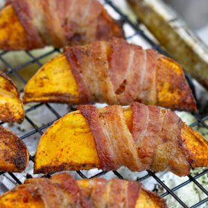 A simple yet delectable recipe, Bacon Wrapped Sweet Potato Wedges are the perfect appetizer or side dish. They are the perfect easy finger food for your holiday party or cookouts. #Glutenfree #Paleo #Whole30 #bacon #recipes #easy #sweetpotatoes #bakedsweetpotatobites #bakedsweetpotatoappetizer #sweetpotatobitesfingerfood #fingerfood #crispysweetpotatobites #appetizerrecipes #sweetpotatorecipes #healthyholidayrecipes #whole30recipes #whole30holidayrecipes #whole30diet