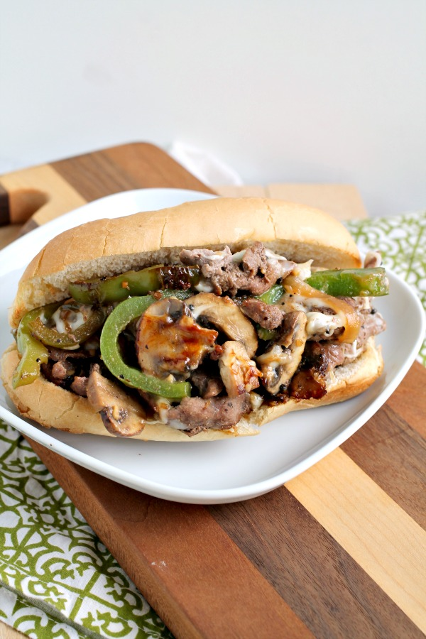 This Grand Escape Steak Sandwich has thinly sliced beef is cooked to perfection, melty cheese, peppers, onions, seasonings, and sauces. #steak #sandwich #recipe #beef #phillycheesesteak #cheesy
