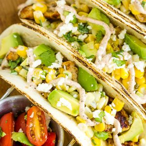 Street Corn Chicken Taco Recipe are loaded with marinated chicken, street corn then topped with avocado, cheese, & sauce! #recipe #TexMex #taco #softtacos #chickentacos #chicken #grilledchicken #corn #streetcorn #avocado #crema