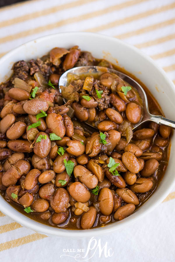 Slow Cooker Pinto Beans and Sausage in a bowl with a spoon garnished with cilantro