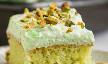 WHIPPED CREAM FROSTED PISTACHIO POKE CAKE